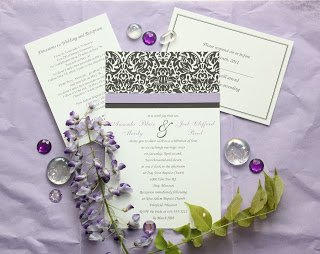 a simple black and white damask pattern across the top of a wedding invitation with purple accents