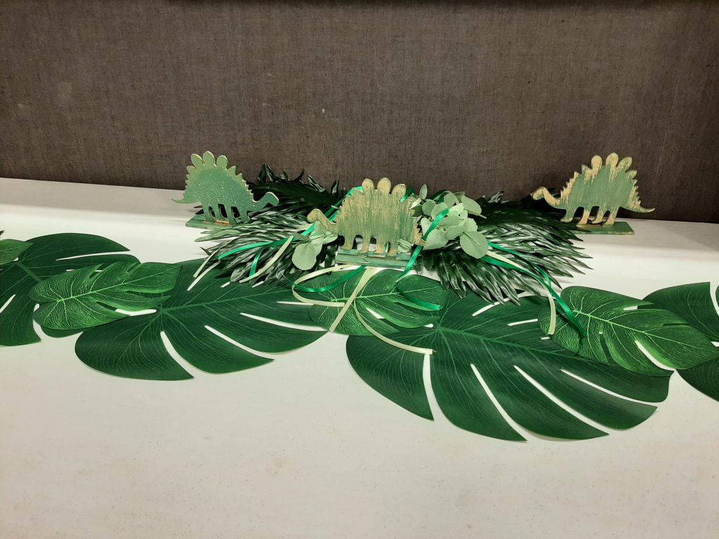 gift table at dinosaur baby shower with big tropical leaves